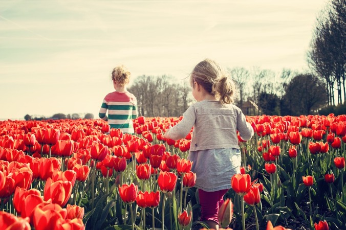 Two children in a field of tulips.
