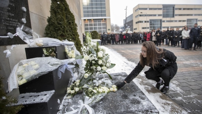 A woman lays roses at the memorial for the 14 women killed in 1989
